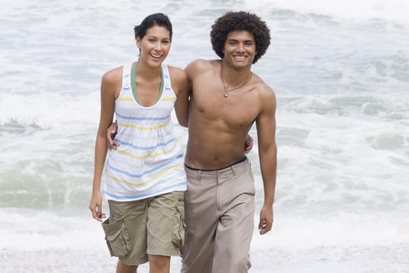 Multi-ethnic couple walking on beach