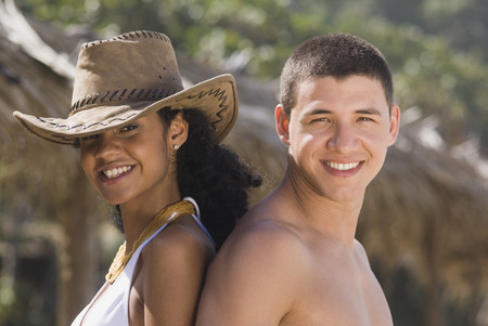 African woman standing back to back with boyfriend