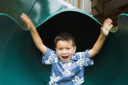 Mixed race boy sliding in playground Imagens