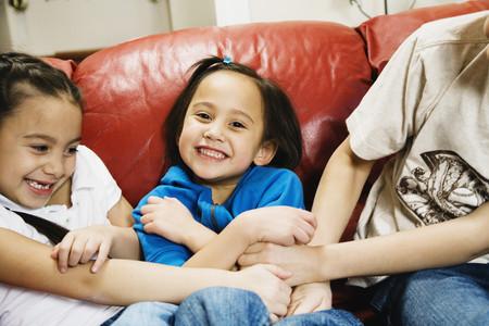 Asian siblings tickling sister Stock Photo