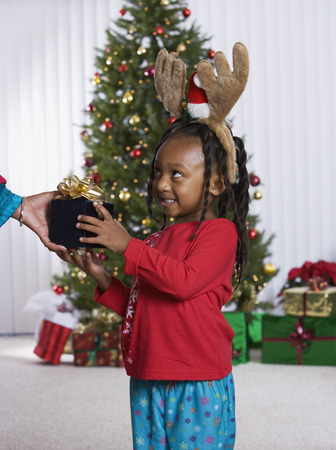 African girl accepting Christmas gift Stock Photo