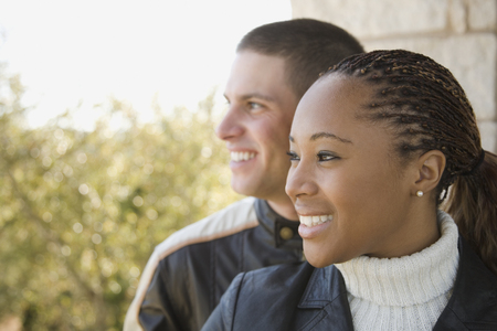 Multi-ethnic couple looking at view on balcony Stock Photo - 108024145