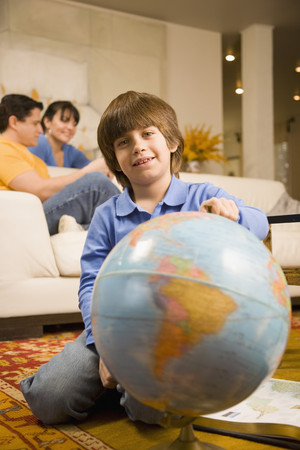 Hispanic boy holding globe