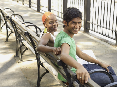 Multi-ethnic couple relaxing on park bench