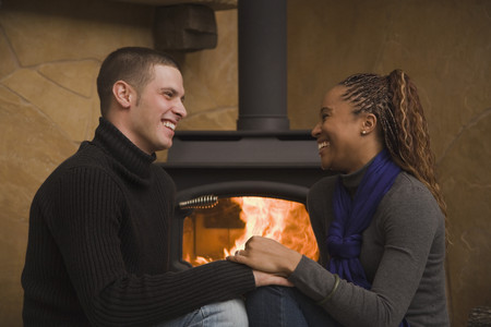 Multi-ethnic couple sitting by wood stove Stock Photo