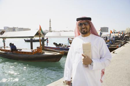 Arab man standing at waterfront Stock Photo
