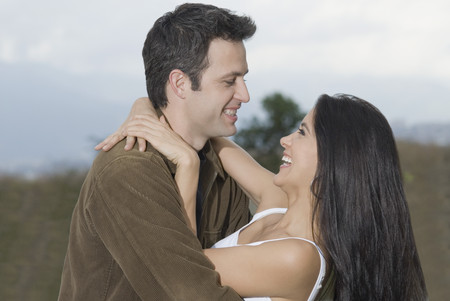 Laughing Hispanic couple hugging Stock Photo