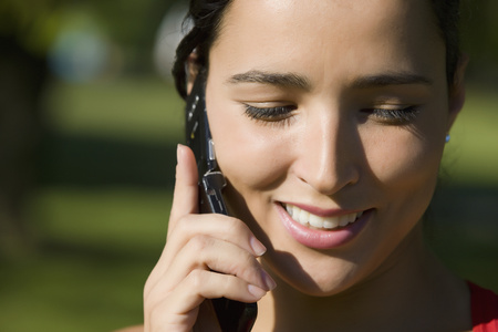 Close up of Hispanic woman talking on cell phone Stock Photo