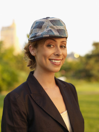 Mixed race woman wearing cap in park Stock Photo