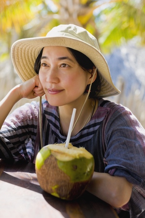 Japanese woman next to coconut Stock Photo