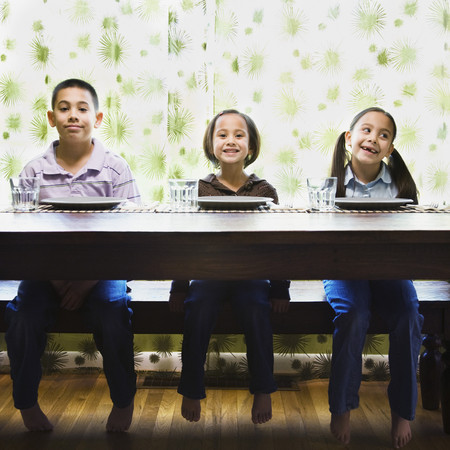 Asian siblings sitting at dinner table Stockfoto
