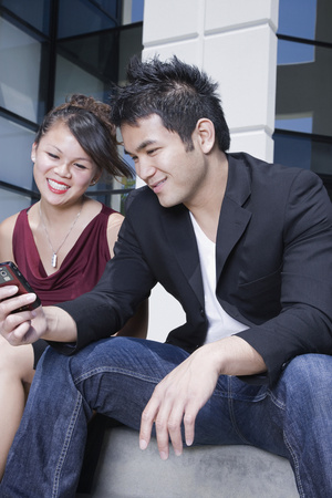Asian man showing cell phone to girlfriend Stock Photo