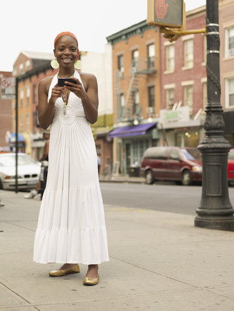 African woman text messaging in urban setting