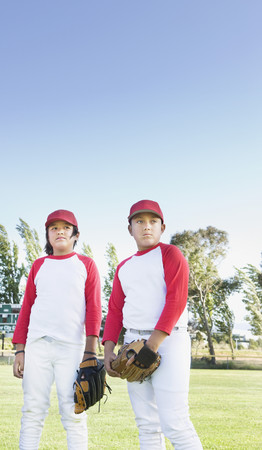 Multi-ethnic boys in baseball uniforms looking pensive