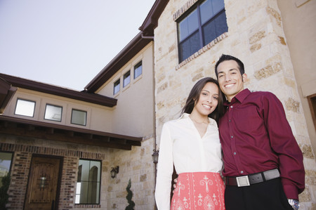Hispanic couple standing outside house