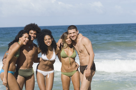 Multi-ethnic friends hugging on beach