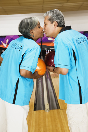 Multi-ethnic couple on bowling team, kissing