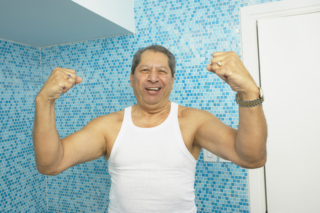 Hispanic man flexing his biceps in bathroom