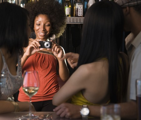 African woman photographing friends in nightclub
