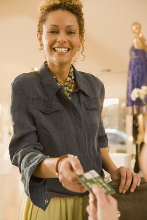 Mixed race woman handing credit card to cashier