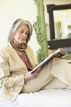 Confident woman relaxing and reading magazine Imagens