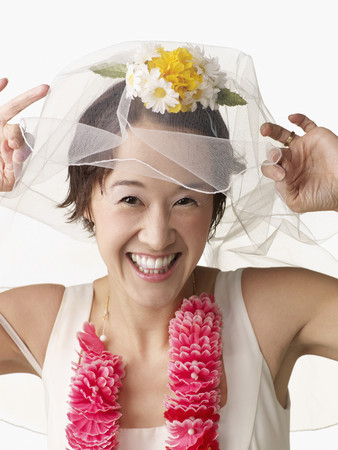 Asian woman in wedding dress and lei Stock Photo