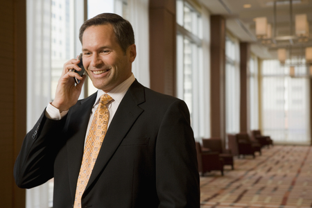 Businessman talking on cell phone in corridor Stock Photo