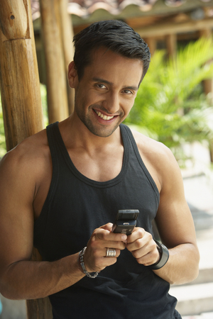 Happy man text messaging on cell phone