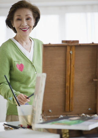 Japanese woman painting on easel Фото со стока