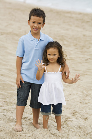 Gemengd ras broer en zus op strand