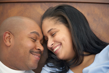Dominican man lounging in bed with wife Standard-Bild - 108065845