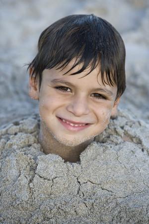 Close up of Hispanic boy buried in sand