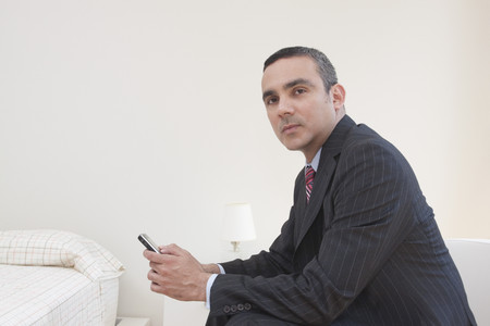 Hispanic businessman holding cell phone