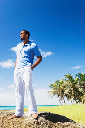 African man standing on rock near ocean