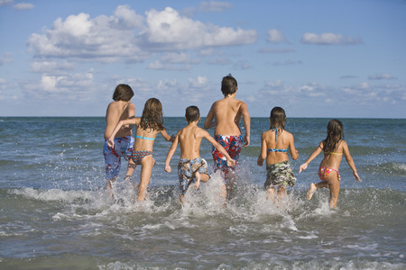Hispanic children running through ocean surf Stok Fotoğraf