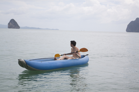 Chinese man paddling boat in ocean Stock Photo
