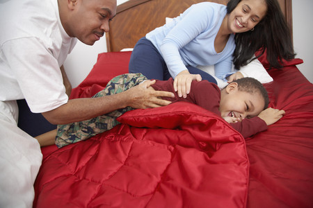 Parents tickling mixed race boy on bed