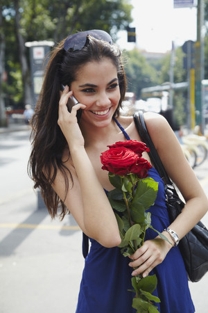 Brazilian woman holding red roses and talking on cell phone Stock Photo