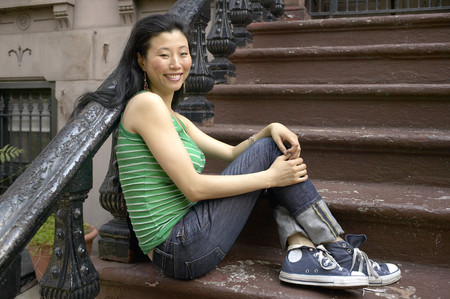 Asian woman sitting on front steps Archivio Fotografico