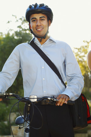Hispanic businessman wearing bike helmet and holding bike