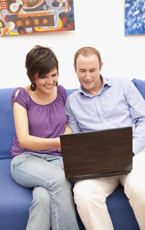 Couple on sofa using laptop together