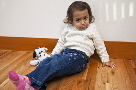 Mixed race girl sitting on floor pouting Stock Photo