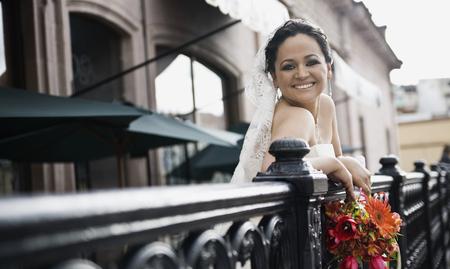 Hispanic bride on balcony smiling