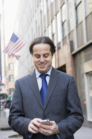 Hispanic businessman text messaging in city Stock Photo