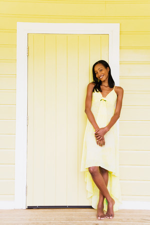 Barefoot African woman leaning against yellow door Stock Photo