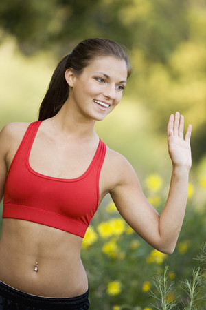 Hispanic woman in sports bra waving