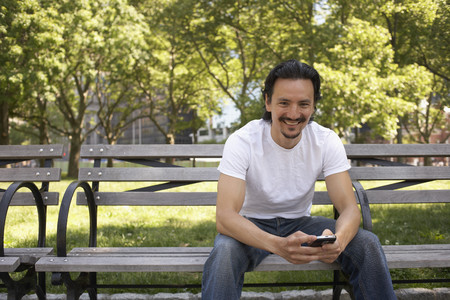 Mixed race man holding cell phone on park bench Stock Photo