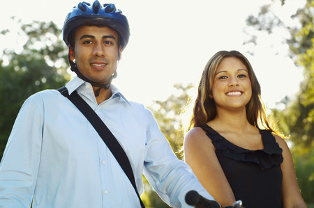 Hispanic man wearing bike helmet posing with girlfriend