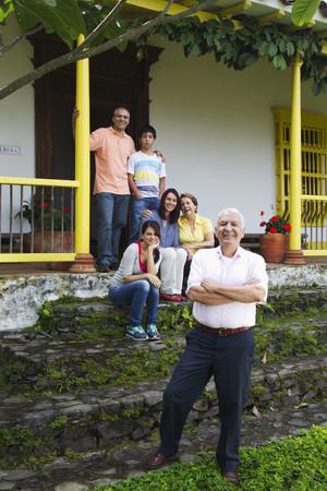 Hispanic family on house steps together Reklamní fotografie