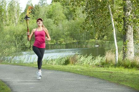 Caucasian athlete running with Olympic torch on park path Imagens